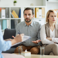 Offended woman with crossed arms looking aside while her husband trying to explaining their problem to counselor